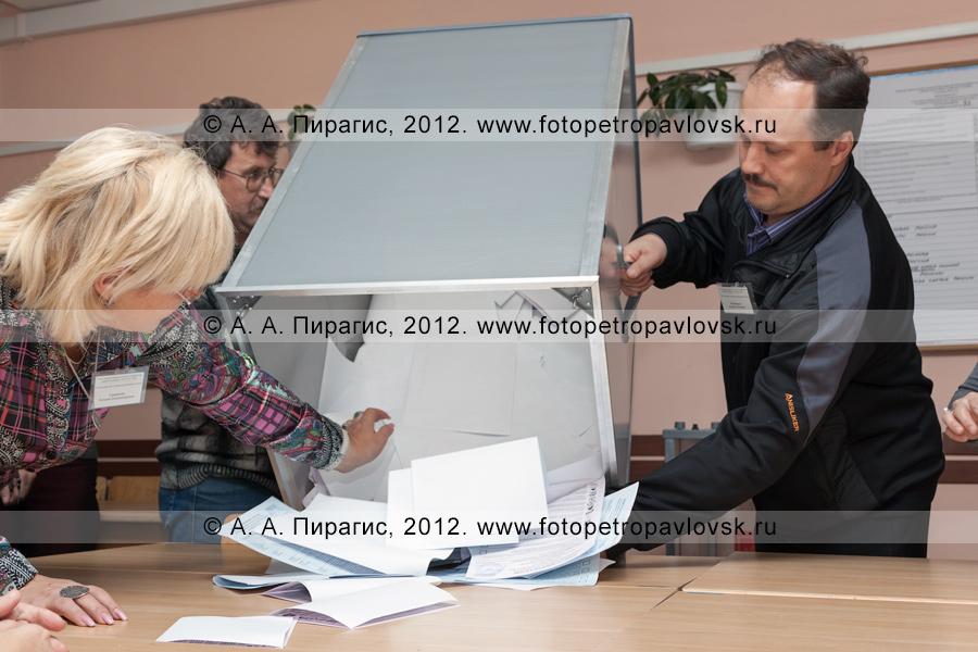 Фотография: извлечение избирательных бюллетеней из стационарной урны для голосования на выборах