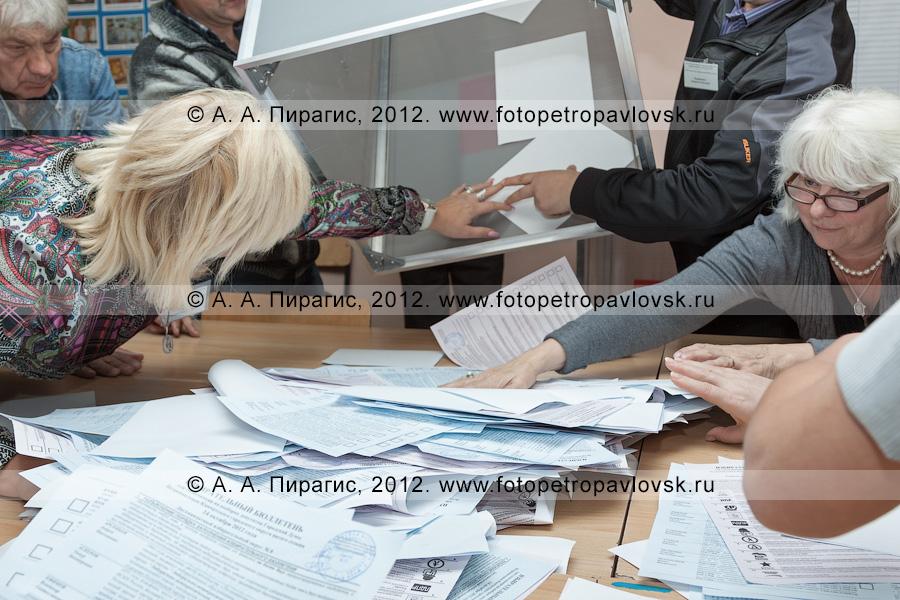 Фотография: сотрудники участковой избирательной комиссии избирательного участка № 51 достают избирательные бюллетени из перевернутой урны для голосования