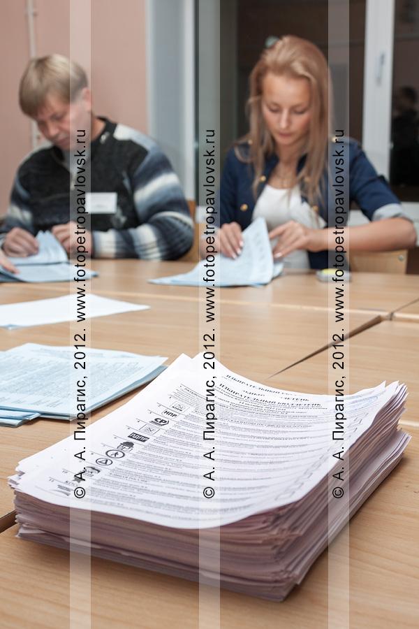 Фотография: стопка избирательных бюллетеней для голосования на выборах на фоне сотрудников участковой избирательной комиссии избирательного участка № 51, ведущих подсчет бюллетеней