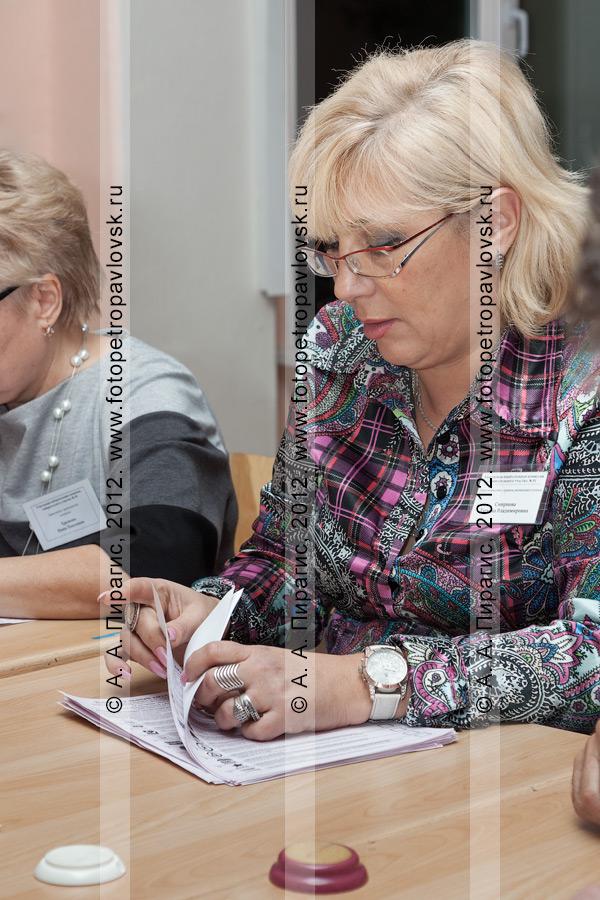 Фотография: член участковой избирательной комиссии избирательного участка № 51 подсчитывает избирательные бюллетени