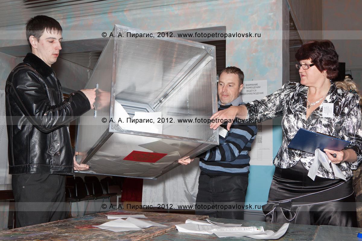 Фотография: члены избирательной комиссии переворачивают вскрытую избирательную урну для голосования на выборах, чтобы достать бюллетени для голосования и начать процедуру подсчета голосов. Выборы Президента России. Избирательный участок № 50, Камчатский край, город Петропавловск-Камчатский