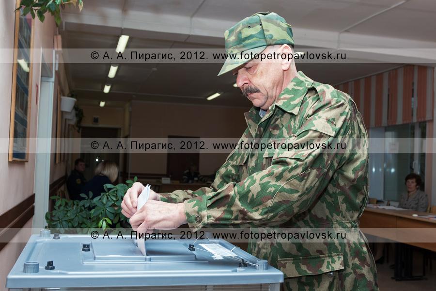 Фотография: житель города Петропавловска-Камчатского голосует на выборах — опускает избирательный бюллетень в стационарную урну для голосования
