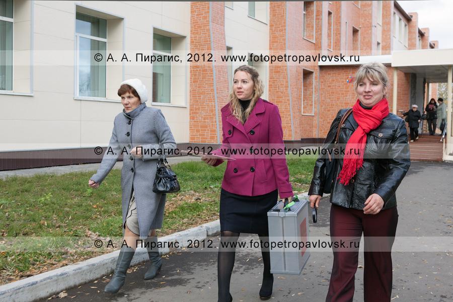Фотография: сотрудники участковой избирательной комиссии избирательного участка № 51 с переносной урной для голосования и наблюдатель идут к избирателям для их голосования вне помещения для голосования