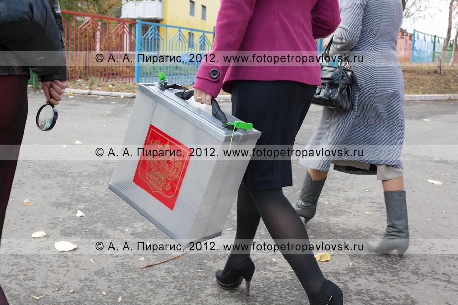 Фотография: сотрудник участковой избирательной комиссии избирательного участка № 51 с переносной урной для голосования вне помещения для голосования идет к избирателям на дом
