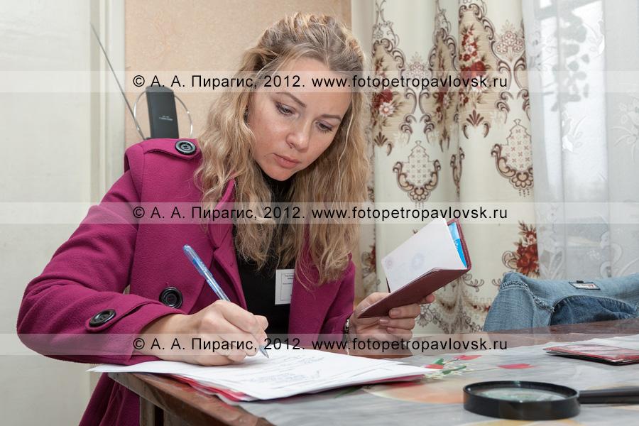 Фотография: член участковой избирательной комиссии избирательного участка № 51 записывает паспортные данные избирателя (голосование вне помещения для голосования)