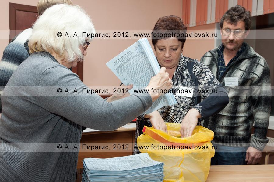Фотография: члены участковой избирательной комиссии избирательного участка № 51 упаковывают гашеные избирательные бюллетени