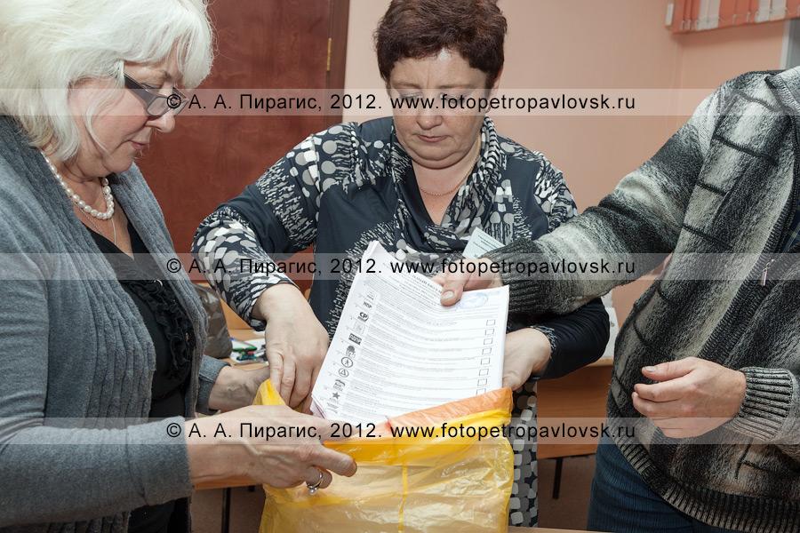 Фотография: сотрудники участковой избирательной комиссии избирательного участка № 51 упаковывают гашеные избирательные бюллетени для голосования