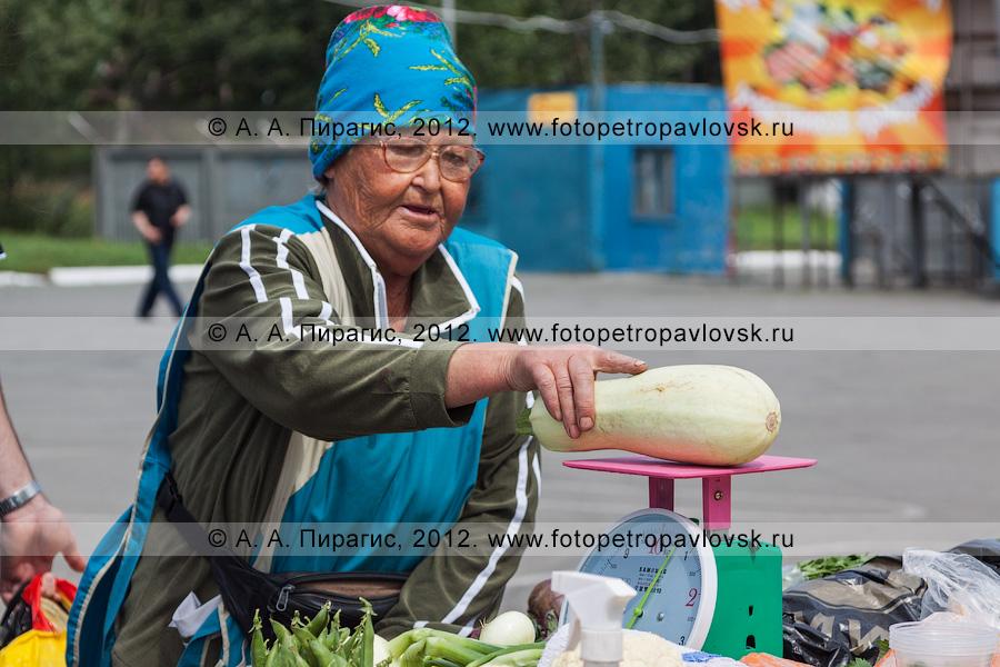 Фотография: продавец взвешивает кабачок. Сельскохозяйственная ярмарка выходного дня в городе Петропавловске-Камчатском