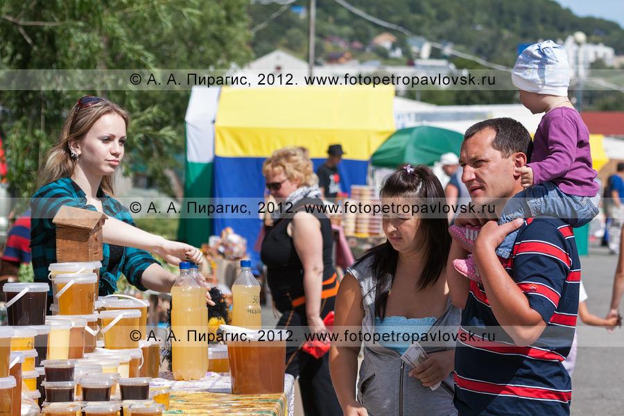 Фотография: продавец и покупатели возле торгового прилавка с медом. Сельскохозяйственная ярмарка выходного дня в столице Камчатского края