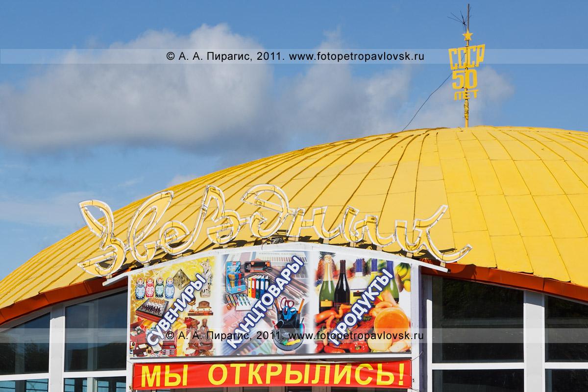 """Фотография: вывеска магазина """"Звездный"""". Под вывеской с названием магазина — рекламный баннер: """"Мы открылись"""". Надпись на шпиле, расположенном на крыше магазина: """"СССР 50 лет"""""""