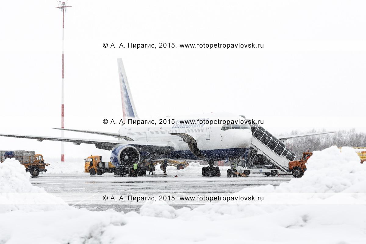 """Службы аэродромно-технического обеспечения аэропорта Петропавловск-Камчатский (аэропорт Елизово) обслуживают самолет Боинг-767 (Boeing-767) авиакомпании """"Трансаэро"""" (Transaero Airlines) во время снегопада. Камчатка"""