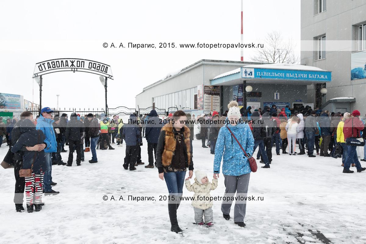 Пассажиры, прилетевшие на Камчатку, и их встречающие в зоне выхода пассажиров с перрона аэропорта и выдачи багажа (павильон выдачи багажа). Аэропорт Петропавловск-Камчатский (аэропорт Елизово)