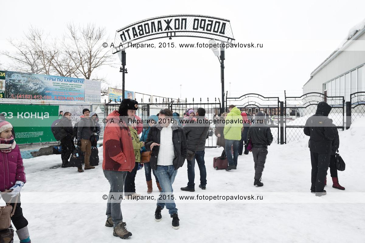 """Пассажиры и встречающие лица возле выхода с перрона аэропорта Петропавловск-Камчатский (аэропорт Елизово). Надпись на арке ворот: """"Добро пожаловать"""""""