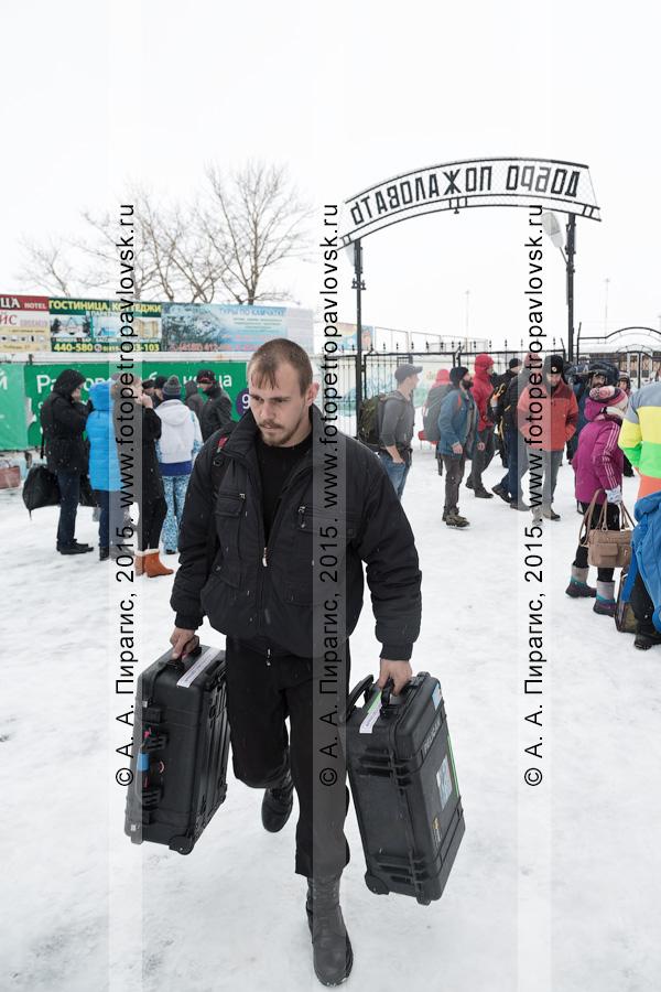 Пассажир с чемоданами идет после получения багажа на фоне выхода с перрона аэропорта Петропавловск-Камчатский (аэропорт Елизово). Камчатский край