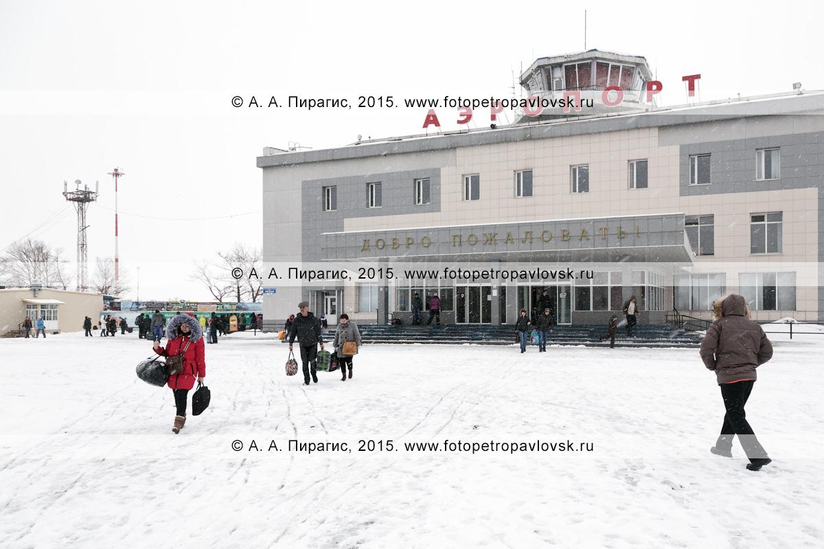 Зимний вид на здание аэровокзала аэропорта Петропавловск-Камчатский (аэропорт Елизово) и привокзальную площадь с людьми. Камчатский край