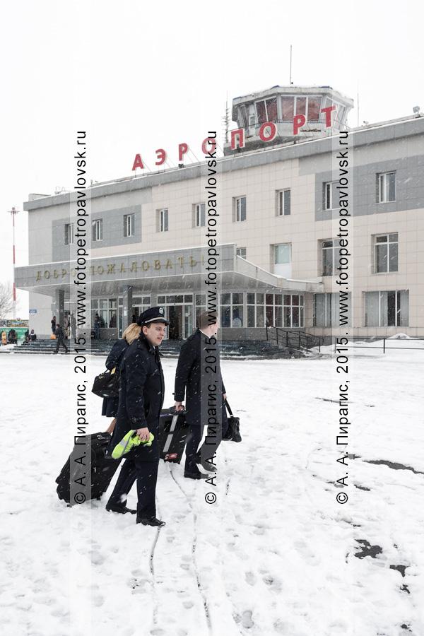 Пилоты с чемоданами идут на фоне аэровокзала аэропорта Петропавловск-Камчатский (аэропорт Елизово) на Камчатке