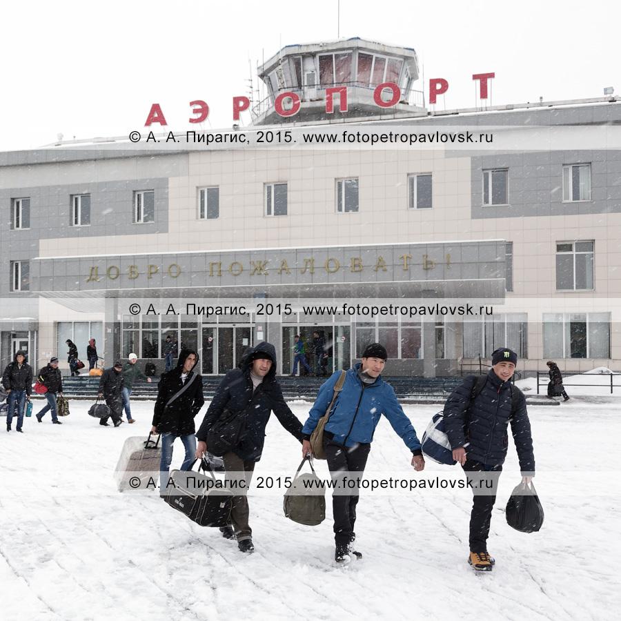 Пассажиры с чемоданами идут на фоне здания аэровокзала аэропорта Петропавловск-Камчатский (аэропорт Елизово) в Камчатском крае