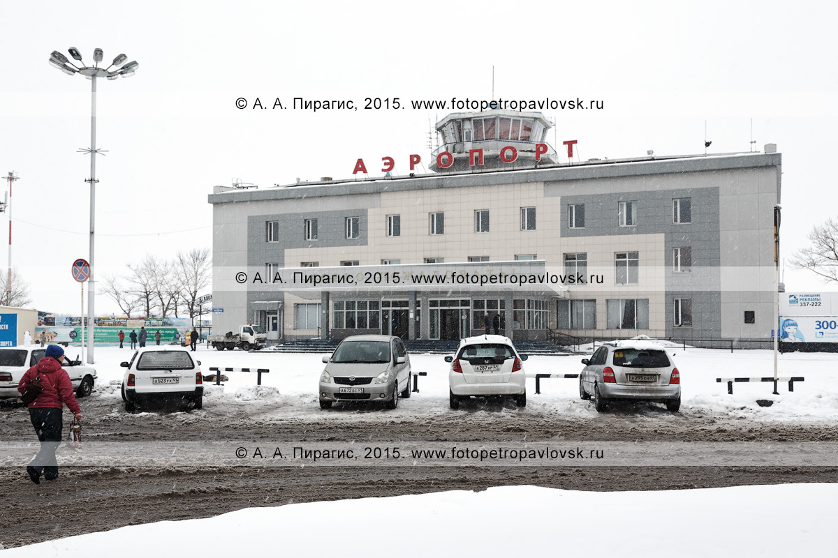 Зимний вид на фасад здания аэропорта Петропавловск-Камчатский (аэропорт Елизово), привокзальную площадь и припаркованные автомобили. Камчатка