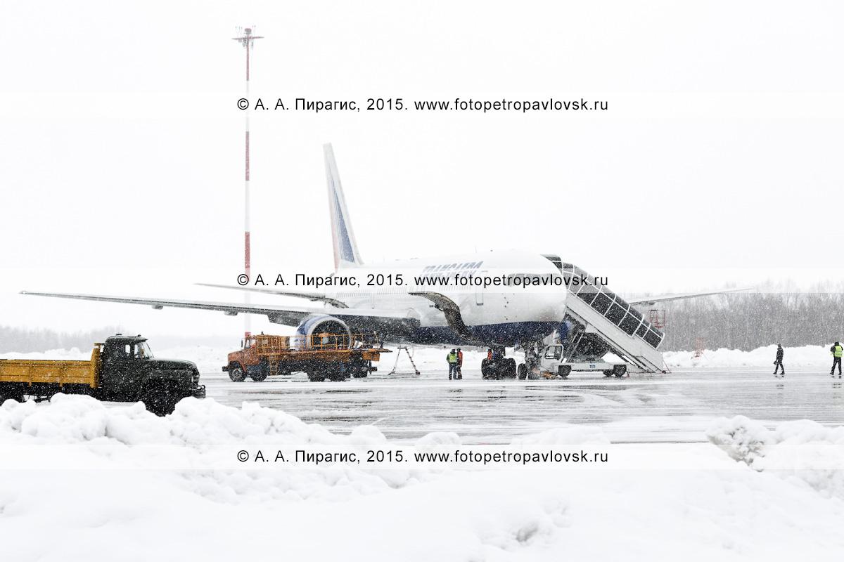 """Специальная аэродромная техника возле самолета Боинг-767 (Boeing-767) авиакомпании """"Трансаэро"""" (Transaero Airlines) в аэропорту Петропавловск-Камчатский (аэропорт Елизово) во время ненастья (снегопад). Камчатка"""