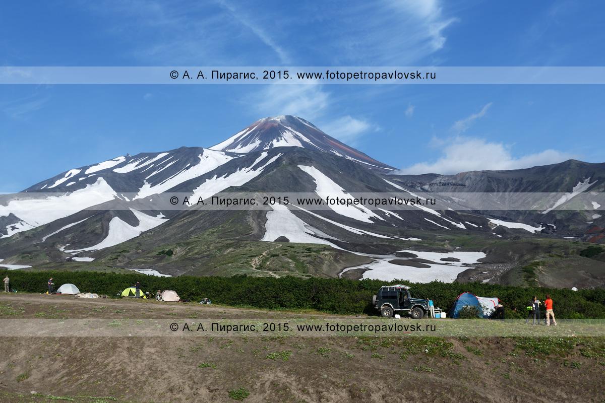 Фотография: камчатский пейзаж — летний вид на Авачинский вулкан (Avachinsky Volcano) и туристический палаточный лагерь у подножия Авачи. Полуостров Камчатка