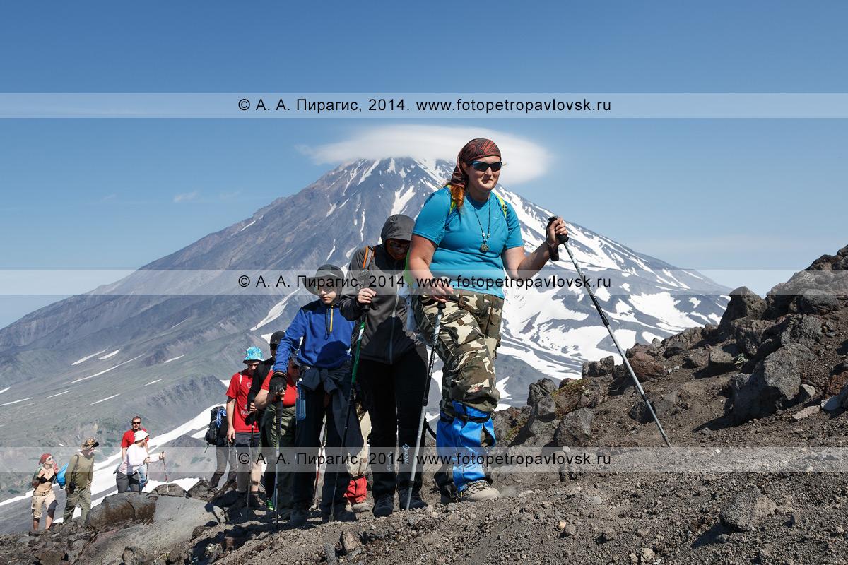 Фотография: группа туристов и путешественников восходит на Авачинский вулкан на Камчатке. На заднем плане: вулкан Корякский