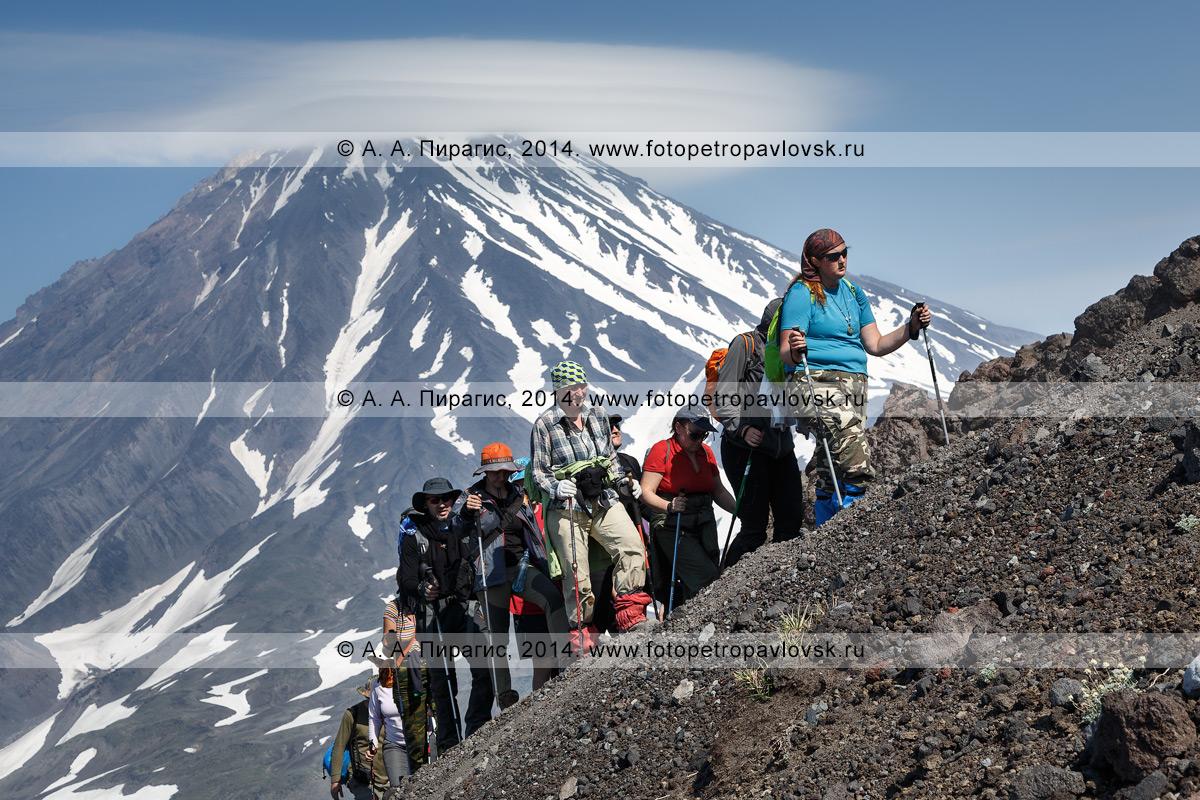 Фотография: пеший туризм на Камчатке — группа туристов и путешественников совершает восхождение на Авачинский вулкан. На заднем плане: Корякский вулкан. Полуостров Камчатка