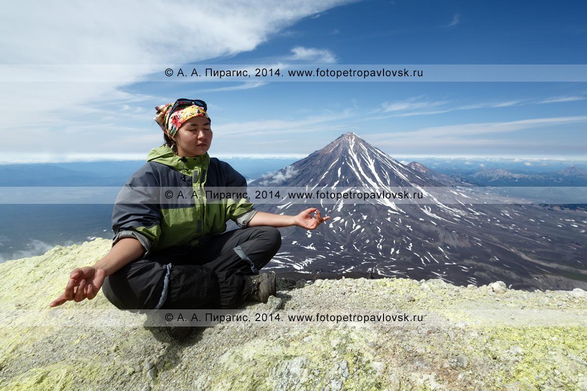 Фотография: девушка-туристка медитирует на вершине действующего вулкана Авачинская сопка на полуострове Камчатка