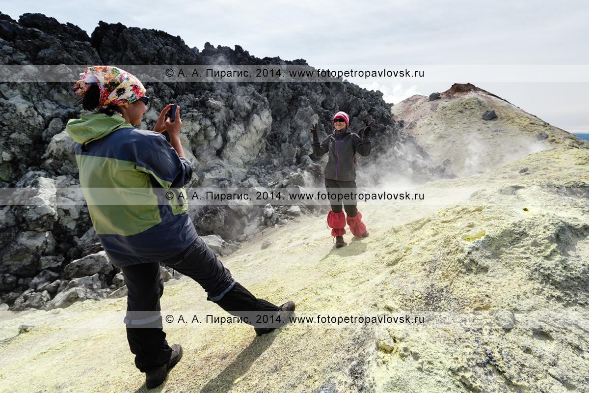 Фотография: веселые девушки-туристки фотографируются на вершине действующего вулкана Авачинская сопка на полуострове Камчатка