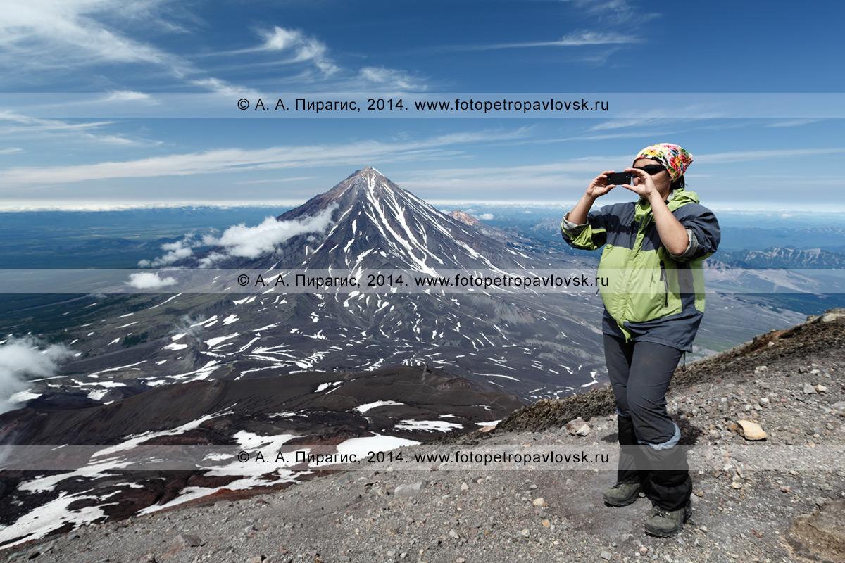 Фотография: девушка-туристка фотографирует на мобильный телефон на вершине Авачинского вулкана на полуострове Камчатка