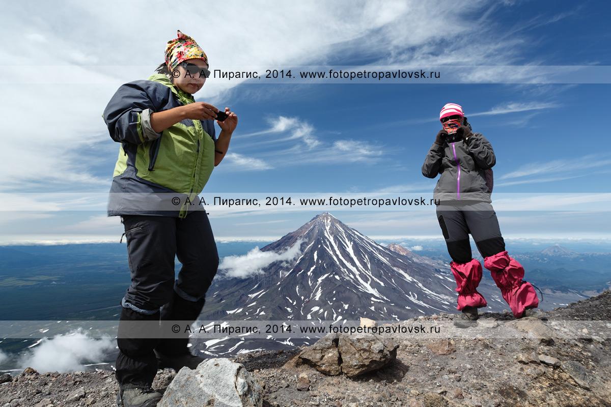 Фотография: девушки-туристки стоят на кромке вершинного кратера Авачинского вулкана на фоне Корякского вулкана. Полуостров Камчатка