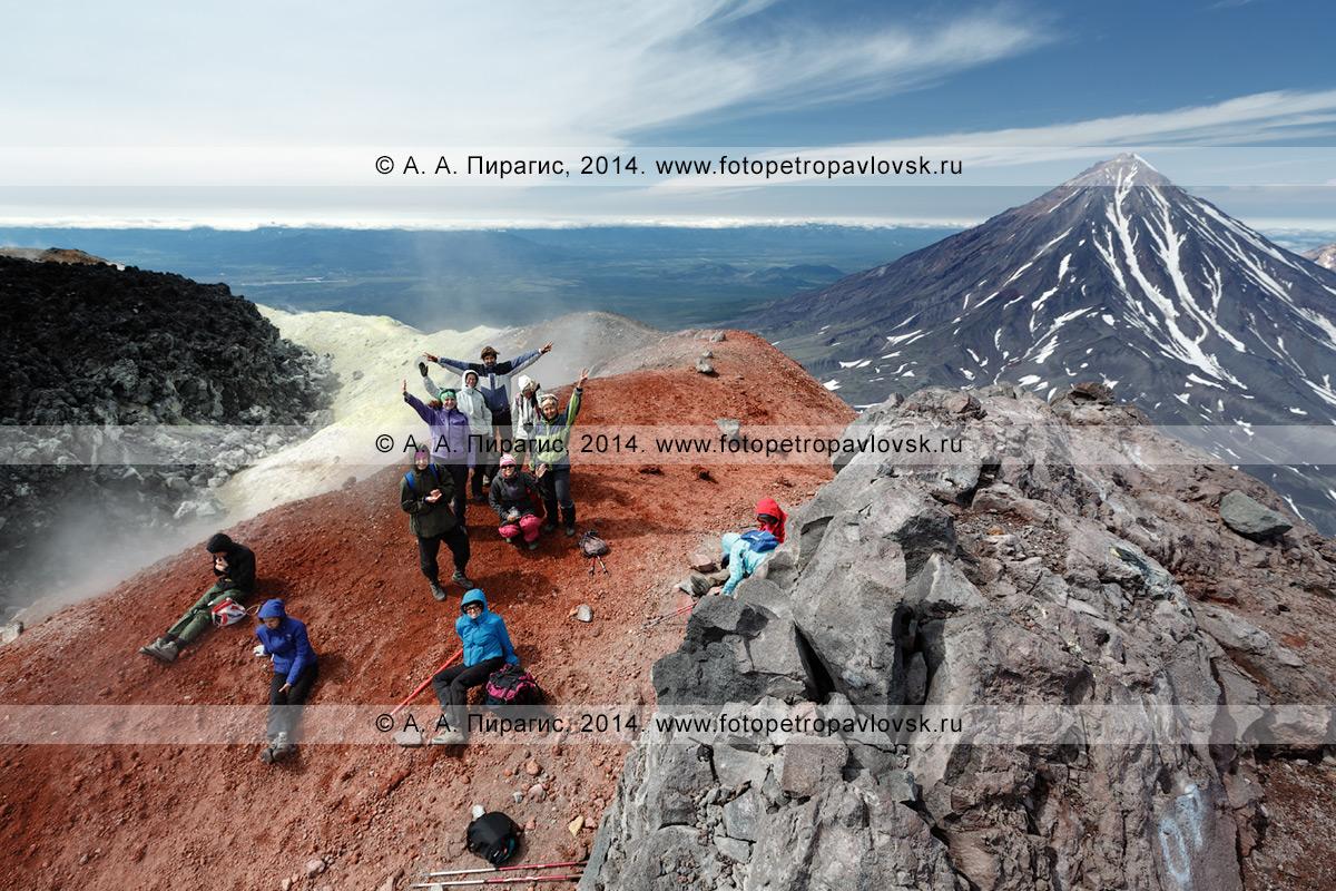 Фотография: пеший туризм на полуострове Камчатка — группа туристов и путешественников отдыхает на вершине действующего вулкана Авачинская сопка после многочасового восхождения