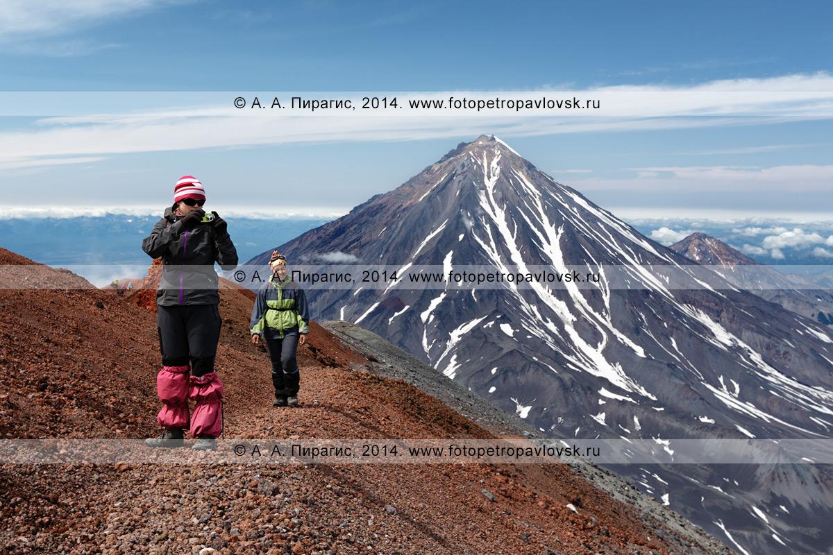 Фотография: пеший туризм на Камчатке — девушки-туристки идут по туристской тропе на вершине Авачинского вулкана на фоне величественного Корякского вулкана