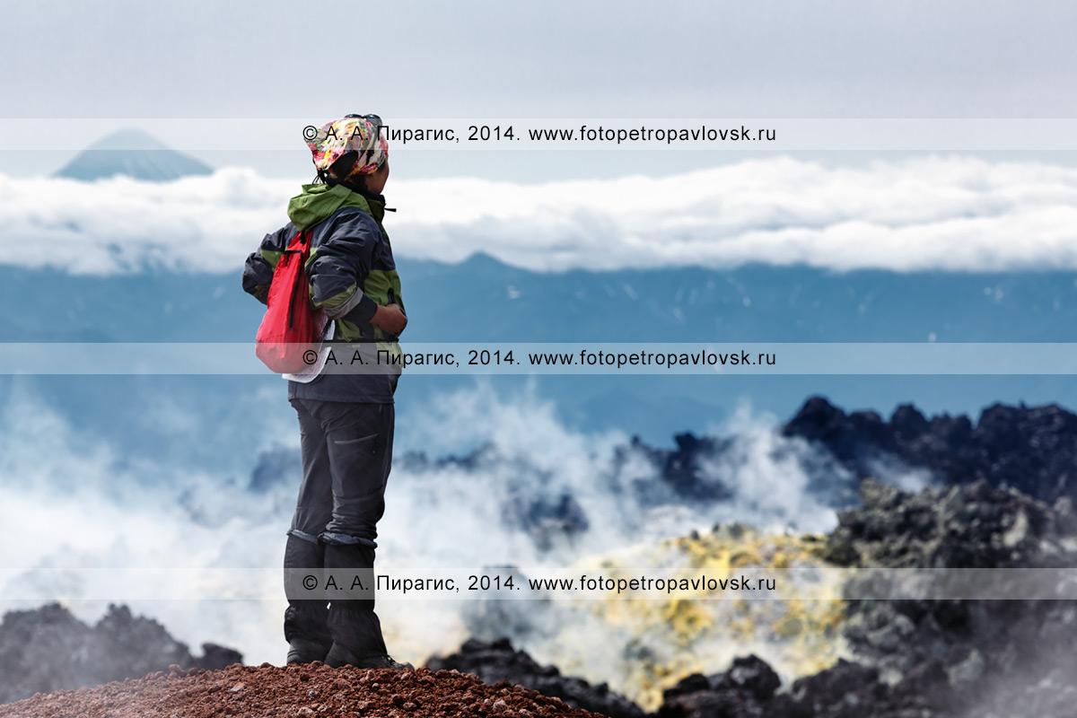 Фотография: пеший туризм на Камчатке — девушка-туристка наслаждается красивым вулканическим ландшафтом в кратере действующего Авачинского вулкана: видом на лавовые потоки, выходы серы и фумаролы, выбрасывающие горячий пар и газ