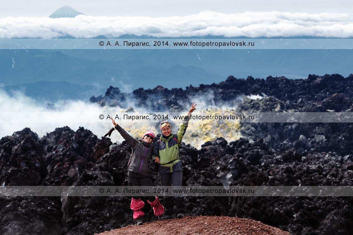 Фотография: пеший туризм на полуострове Камчатка — девушки-туристки стоят в кратере вулкана Авачинская сопка на фоне красивого вида: нагромождения лавы, выходов серы и работающих фумарол, выбрасывающих горячий газ и пар
