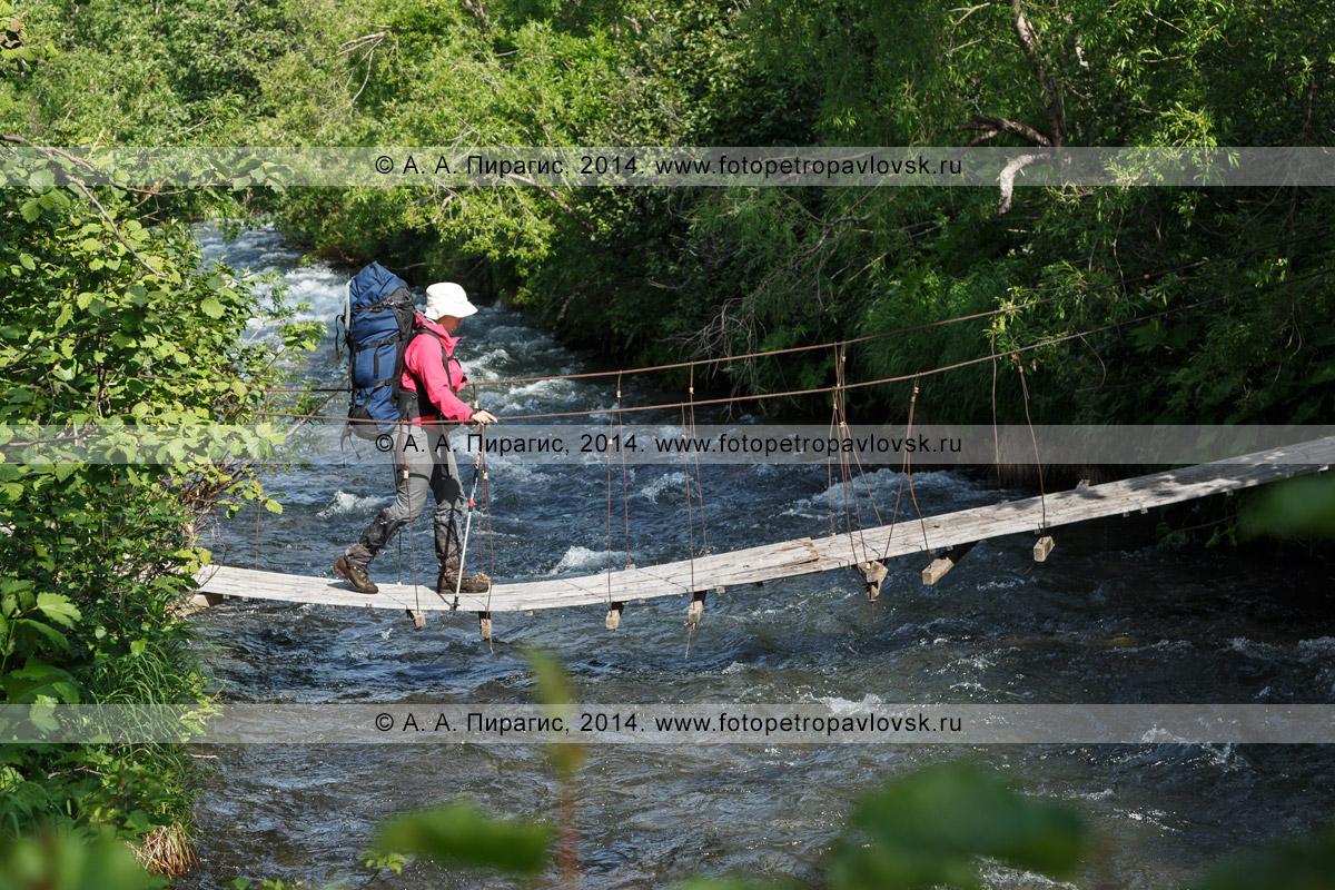 Фотография: девушка-туристка с рюкзаком переправляется через горную реку по пешеходному подвесному мосту (висячему мосту). Полуостров Камчатка, Налычевская долина