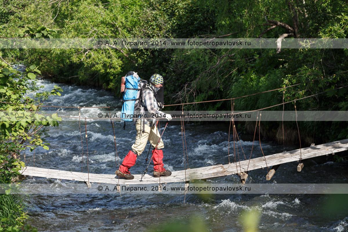 Фотография: женщина-туристка с рюкзаком за плечами идет по висячему мосту (подвесному мосту) через горную реку. Полуостров Камчатка, Налычевский природный парк