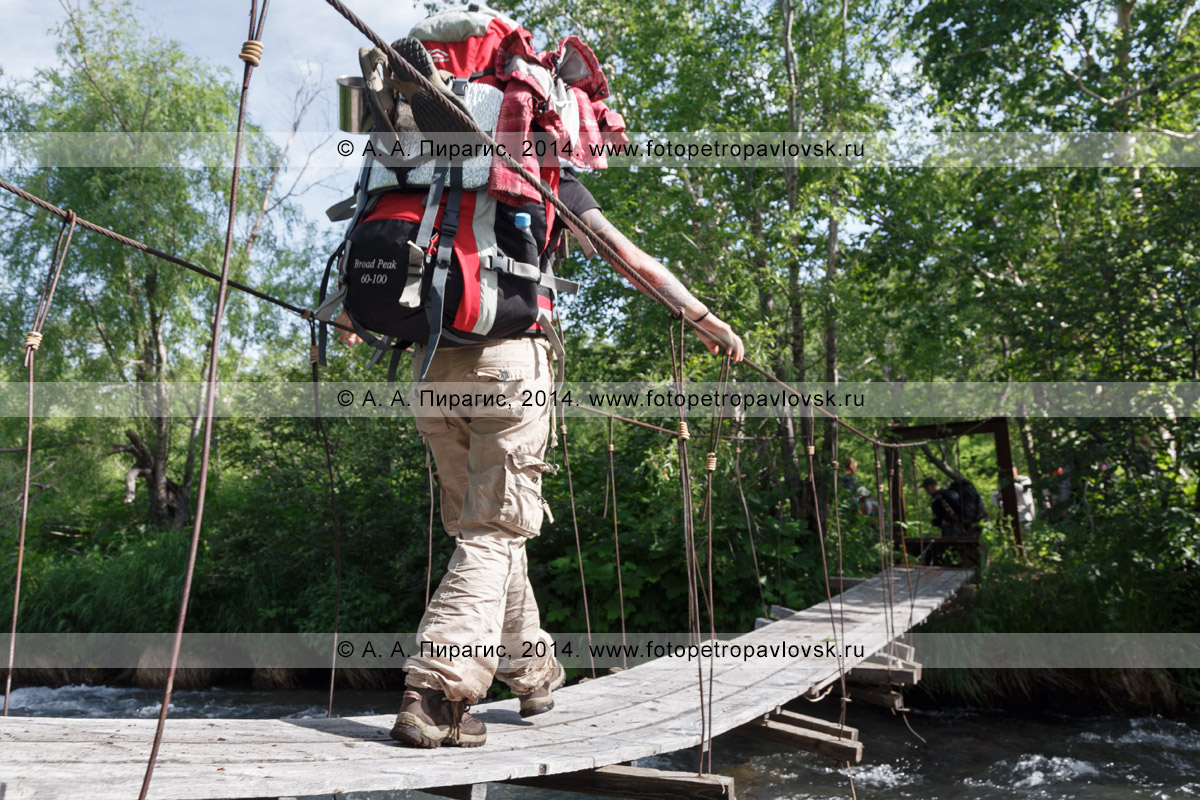 Фотография: девушка-туристка с рюкзаком за плечами идет по подвесному мосту (висячему мосту) через горную реку. Камчатка, Налычевский природный парк