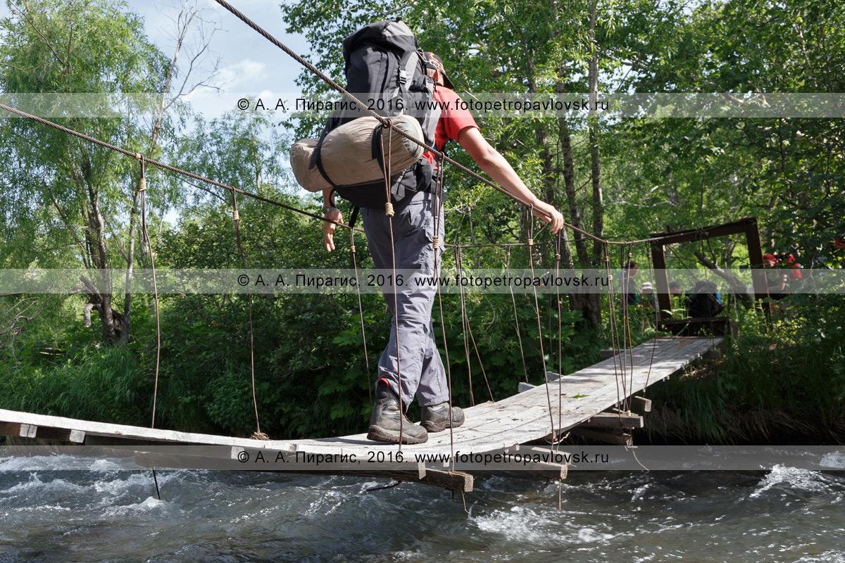 Фотография: турист с рюкзаком за плечами переходит по пешеходному висячему мосту (подвесному мосту) через горную реку. Камчатка, Налычево
