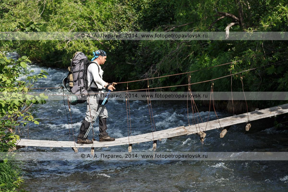 Фотография: турист с огромным рюкзаком за плечами переходит через горную реку по пешеходному подвесному мосту (висячему мосту). Камчатский край, Налычево