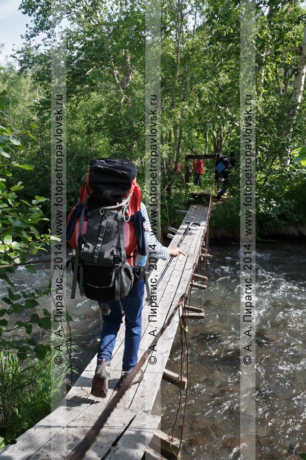 Фотография: девушка-туристка с огромным рюкзаком переходит через горную реку по подвесному мосту (висячему мосту). Налычево, Камчатский край