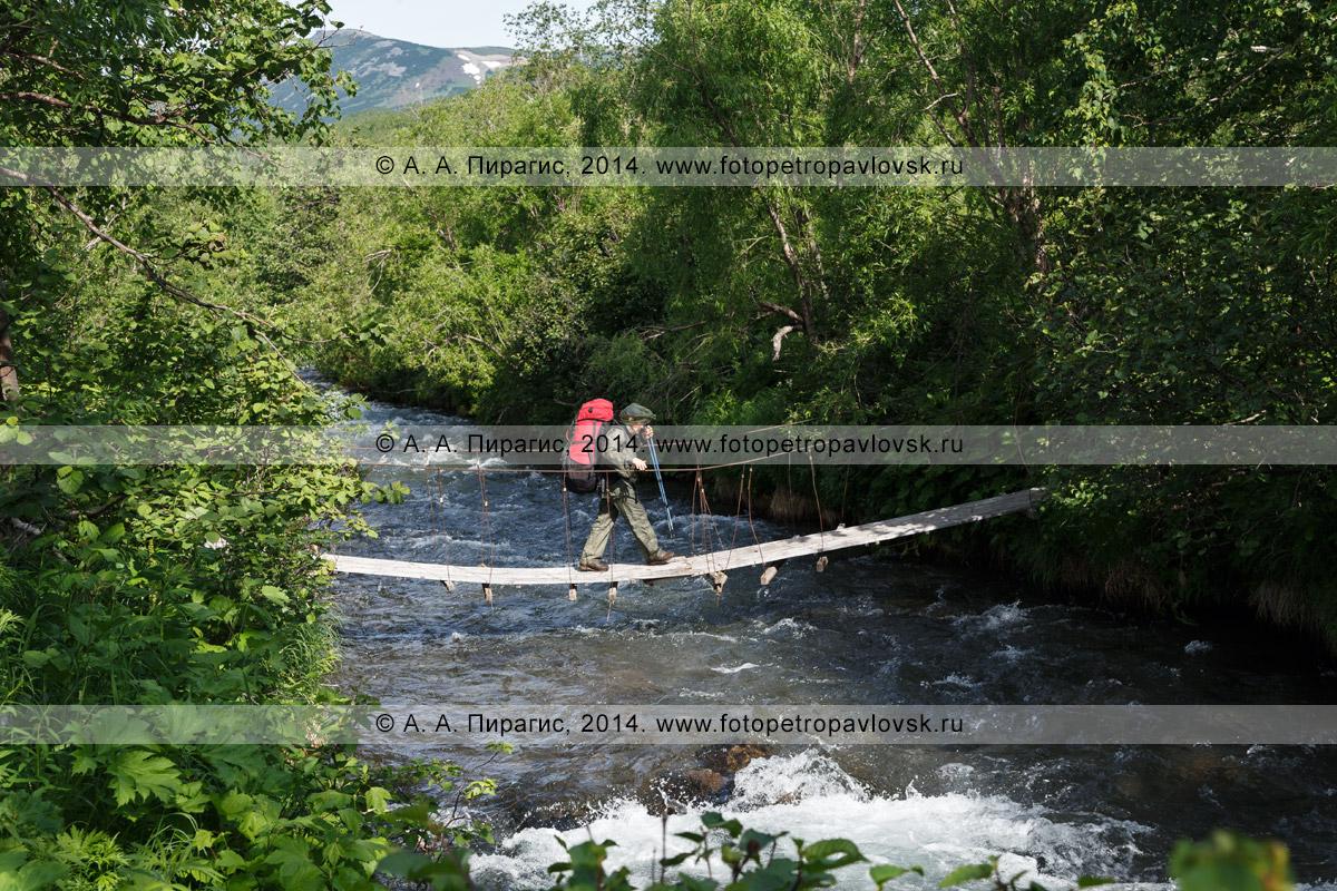 Фотография: женщина-туристка с рюкзаком за плечами переходит через горную реку по висячему мосту (подвесному мосту). Налычево, полуостров Камчатка