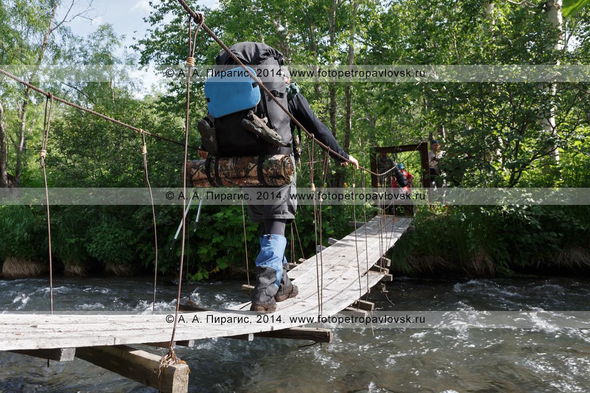 Фотография: турист и путешественник с рюкзаком за плечами переходит по подвесному мосту (висячему мосту) через горную реку. Налычево, Камчатский край