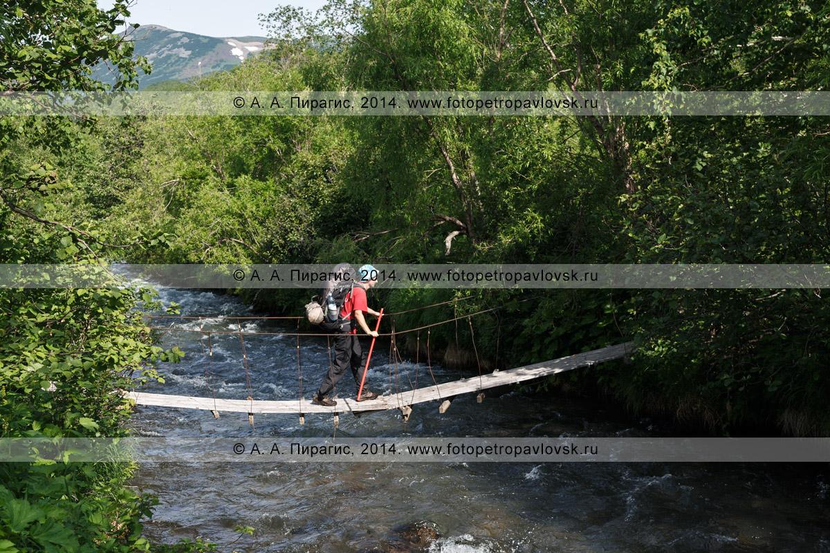 Фотография: турист с рюкзаком за плечами переходит по пешеходному подвесному мосту (висячему мосту) через горную реку. Налычево, Камчатский край
