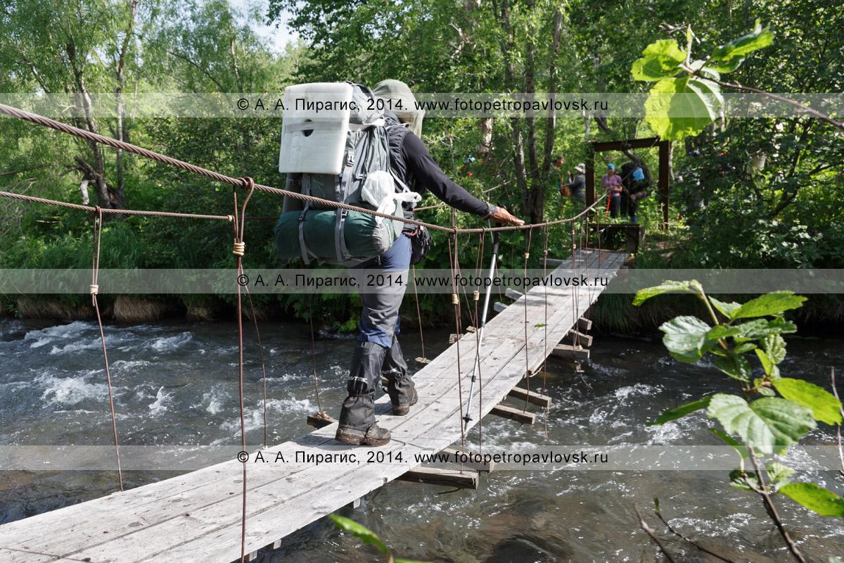 Фотография: турист с рюкзаком за плечами идет по пешеходному висячему мосту (подвесному мосту) через горную реку. Налычево, полуостров Камчатка