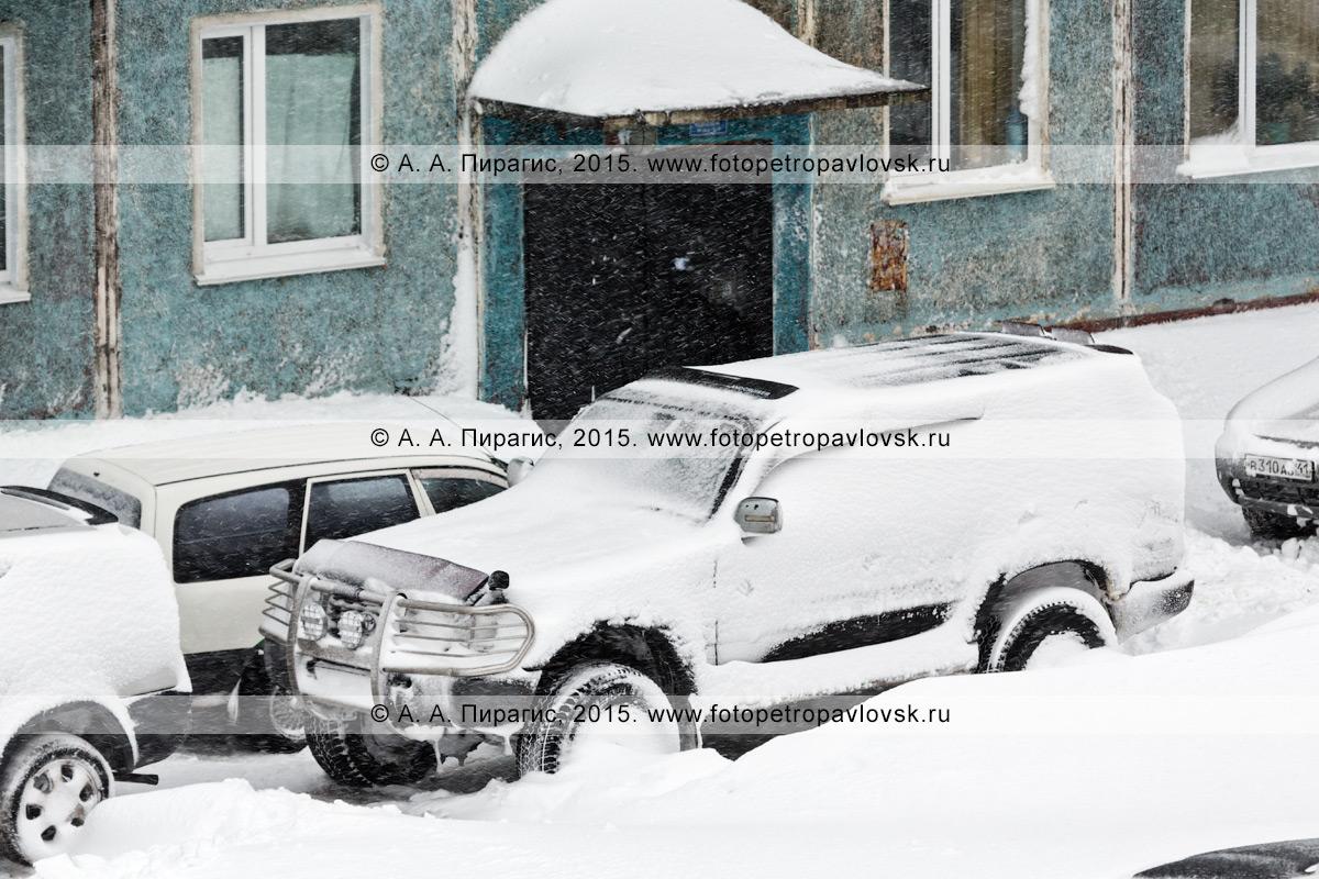 Внедорожник (джип), припорошенный снегом во время пурги (метели) в Петропавловске-Камчатском, стоит возле подъезда жилого дома