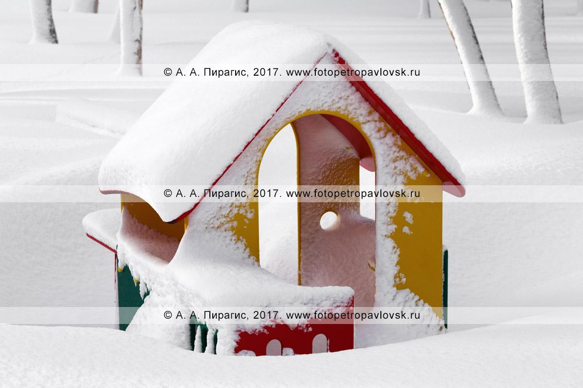 Фотография: занесенный снегом детский уличный игровой домик, детская игровая площадка в парке зимой