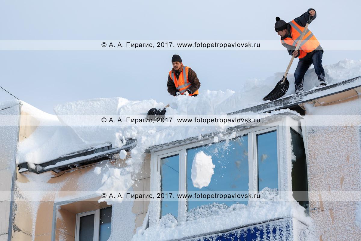 Фотография: зимняя очистка кровли жилого здания от снега и наледи после снежного циклона. Камчатский край