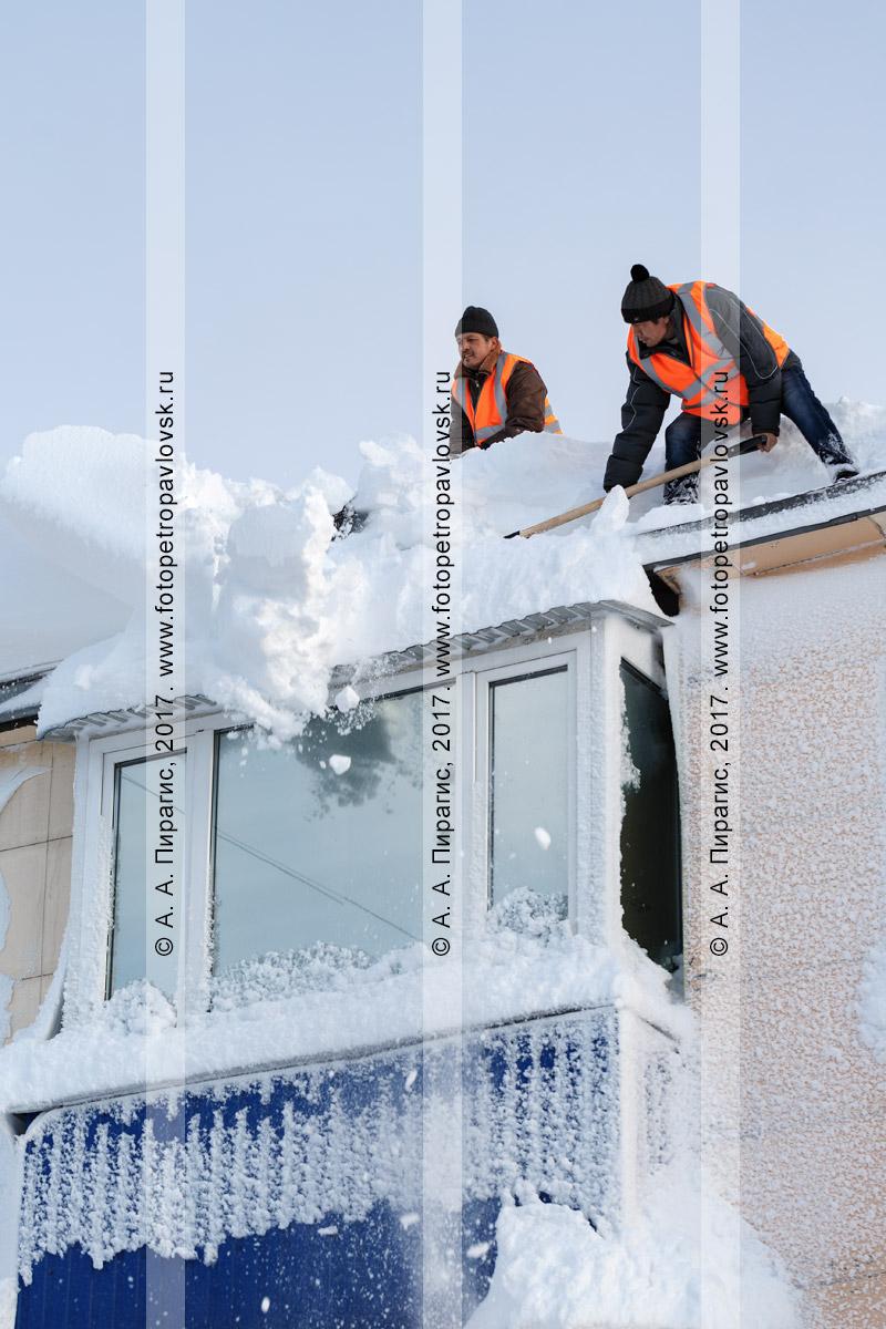 Фотография: рабочие выполняют работы по зимней очистке крыши жилого здания от снега и наледи после мощного циклона (метели, пурги). Город Петропавловск-Камчатский