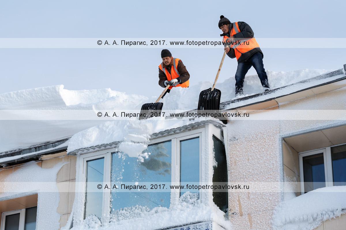 Фотография: рабочие сбрасывают пластмассовыми лопатами снег с крыши жилого дома после пурги в Петропавловск-Камчатском городском округе
