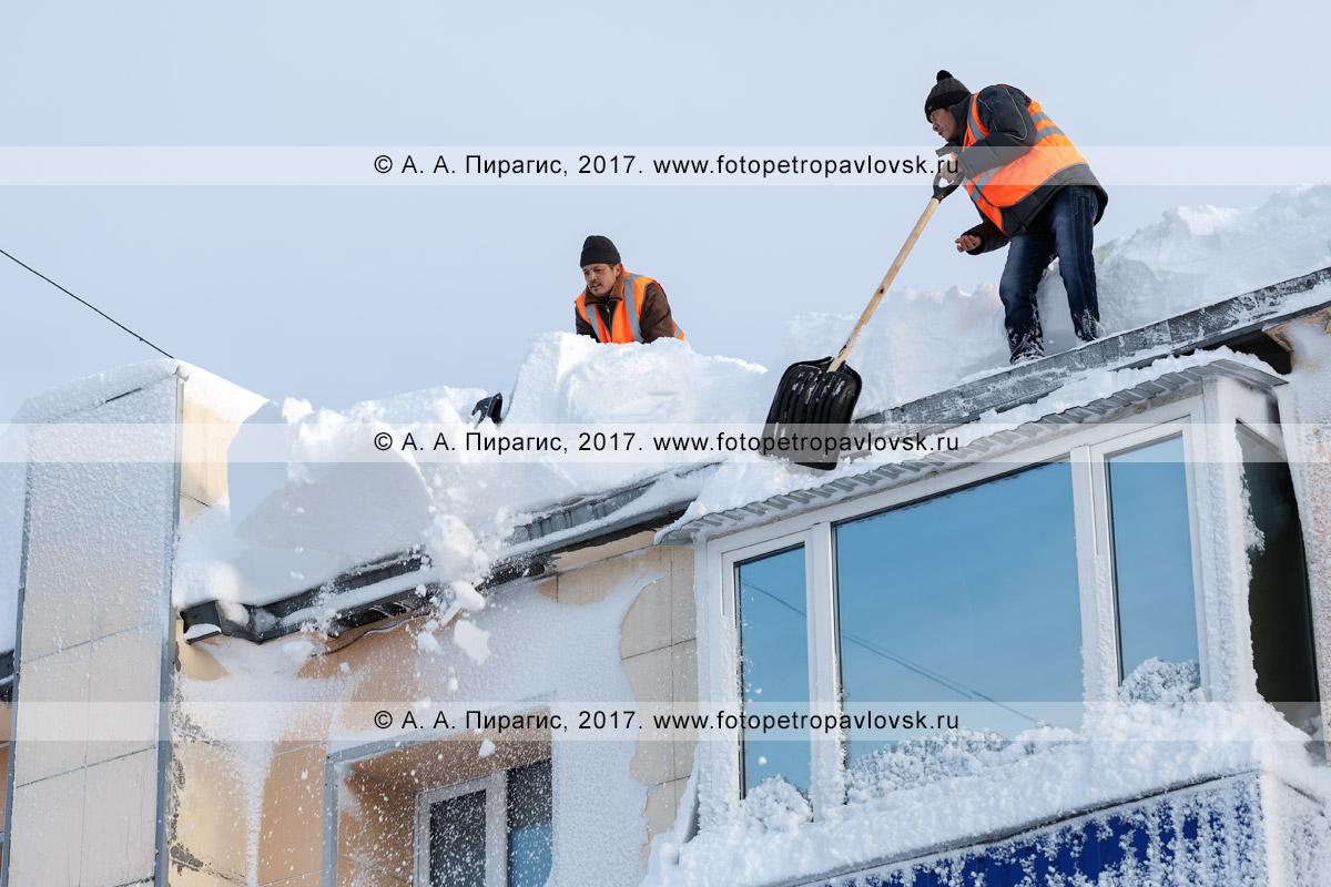 Фотография: рабочие без страховки сбрасывают лопатами снег с крыши жилого многоэтажного дома после пурги в городе Петропавловске-Камчатском